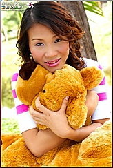 Hiroko Rumi Seated Clutching Teddy Bear Wearing Pink Striped Top