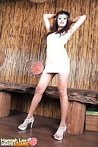 Arms raised above her head in short dress in high heels