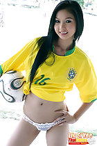 Long hair falling over her brazil football shirt clutching a ball under her arm hand on hip wearing white panties