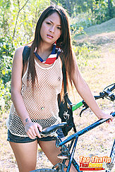 Standing Beside Bicycle Long Hair Wearing String Vest In Shorts