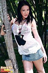 Standing Against Tree Wearing White Top In Denim Short Skirt