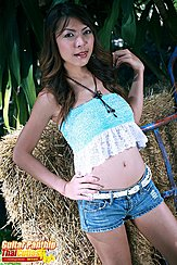 Standing Beside Hay Bale Wearing Cropped Top In Denim Shorts Hand On Hip Playing With Her Long Hair
