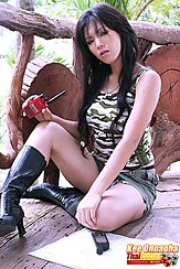 Seated On Floor Wearing Camo Top In Black Boots Long Hair