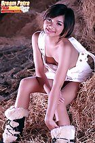 Dream Patra seated on hay bale leaning forward in white dungarees wearing boots