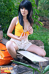 Sitting Astride Bench Wearing Orange Top In Shorts