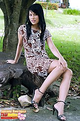 Sitting On Tree Stump Wearing Dress In High Heels