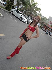 Standing In Street Wearing Brief Red Top In Black Shorts Hand On Hip
