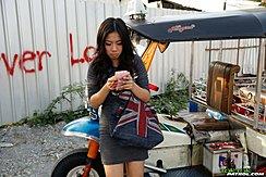 Standing Beside Tuktuk Looking At Her Phone